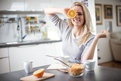 Schöne blonde kaukasische Frau, die in ihrer Küche, beim Trinken in Kaffee oder in Tee und eine gesunde Frühstücksmahlzeit des Ce Stockfoto