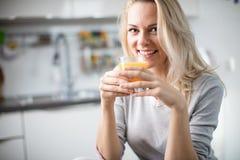 Schöne blonde kaukasische Frau, die in ihrer Küche, beim Trinken in Kaffee oder in Tee und eine gesunde Frühstücksmahlzeit des Ce Stockfotografie