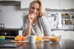 Schöne blonde kaukasische Frau, die in ihrer Küche, beim Trinken in Kaffee oder in Tee und eine gesunde Frühstücksmahlzeit des Ce Stockfotos