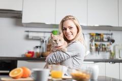 Schöne blonde kaukasische Frau, die in ihrer Küche, beim Trinken in Kaffee oder in Tee und eine gesunde Frühstücksmahlzeit des Ce Lizenzfreie Stockfotografie
