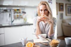 Schöne blonde kaukasische Frau, die in ihrer Küche, beim Trinken in Kaffee oder in Tee und eine gesunde Frühstücksmahlzeit des Ce Lizenzfreies Stockbild