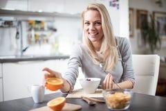 Schöne blonde kaukasische Frau, die in ihrer Küche, beim Trinken in Kaffee oder in Tee und eine gesunde Frühstücksmahlzeit des Ce Lizenzfreie Stockbilder
