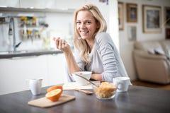 Schöne blonde kaukasische Frau, die in ihrer Küche, beim Trinken in Kaffee oder in Tee und eine gesunde Frühstücksmahlzeit des Ce Stockbild