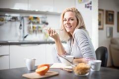 Schöne blonde kaukasische Frau, die in ihrer Küche, beim Trinken in Kaffee oder in Tee und eine gesunde Frühstücksmahlzeit des Ce Lizenzfreie Stockfotos