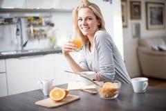 Schöne blonde kaukasische Frau, die in ihrer Küche, beim Trinken in Kaffee oder in Tee und eine gesunde Frühstücksmahlzeit des Ce Lizenzfreies Stockfoto
