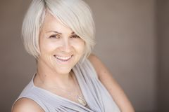 Schöne blonde kaukasische Frau mit dem stilvollen Haarschnitt, der nett in der Kamera auf einem unscharfen blauen Hintergrund sch Stockfoto