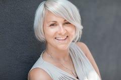 Schöne blonde kaukasische Frau mit dem stilvollen Haarschnitt, der nett in der Kamera auf einem unscharfen blauen Hintergrund sch Lizenzfreies Stockfoto