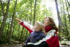 Schöne blonde kleine Tochtermama im Wald Stockfoto