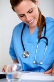 Schöne blonde Krankenschwester, die mit einem Stethoskop lächelt Lizenzfreie Stockfotos
