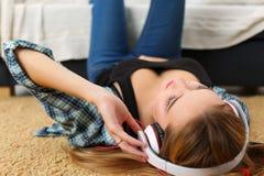 Schöne blonde lächelnde Frau, die auf Teppichboden tragendem hea liegt Stockfoto