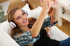 Schöne blonde lächelnde Frau, die auf weißer Couch liegt Stockbild
