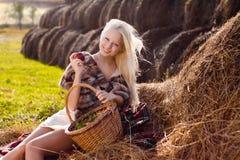 Schöne blonde lächelnde Frau mit Apfel Stockfotos
