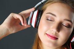 Schöne blonde lächelnde Frau mit Augen schloss tragendes headphon Lizenzfreie Stockfotografie