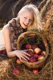 Schöne blonde lächelnde Frau mit vielen Apfel Stockbild