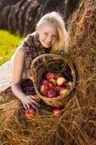 Schöne blonde lächelnde Frau mit vielen Apfel Lizenzfreie Stockfotografie