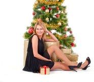 Schöne blonde lächelnde Frau und der Weihnachtsbaum Stockfoto