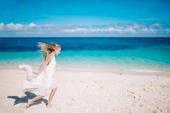 Schöne blonde lange Haarbraut im langen weißen Kleid, das auf dem weißen Sandstrand läuft Stockfotografie