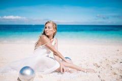 Schöne blonde lange Haarbraut im langen weißen Kleid, das auf dem weißen Sandstrand mit einer Perle sitzt Stockfoto