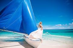 Schöne blonde lange Haarbraut im langen weißen Kleid des offenen Rückens mit Perlen Sie bleibt auf dem blauen Segelboot Blauer Hi Stockbild