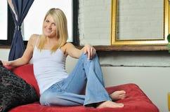 Schöne blonde lounging Frau - Jeans und Becken   Stockfoto