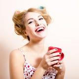 Schöne blonde lustige blonde Frau der grünen Augen des Pinupmädchens mit glücklichem lächelndem schauendem trinkendem Tee der Kame Lizenzfreie Stockfotos