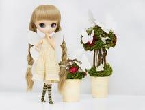 Schöne blonde Mädchenpuppe umgibt viele weißen Schmetterlinge Stockfoto