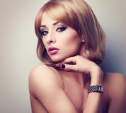 Schöne blonde Make-upfrau, die in Mode Uhren auf dem h aufwirft Stockbilder