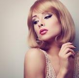 Schöne blonde Make-upfrau mit der kurzen Frisur, die unten schaut Stockbild