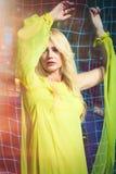 Schöne blonde Modefrau in der langen eleganten gelben Kleiderhaltung im Vergnügungsparksommer stockbild