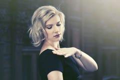 Schöne blonde Modefrau im schwarzen Kleidergehen im Freien Stockfotografie