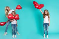 Schöne blonde Mutter und die Tochter, die rotes Valentinsgruß ` s hält, steigt im Ballon auf Lizenzfreie Stockfotografie