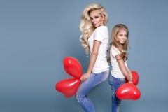 Schöne blonde Mutter und die Tochter, die rotes Valentinsgruß ` s hält, steigt im Ballon auf Lizenzfreie Stockfotos