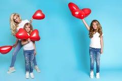 Schöne blonde Mutter und die Tochter, die rotes Valentinsgruß ` s hält, steigt im Ballon auf Stockfotos