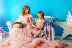Schöne blonde Mutter und Tochter, die auf der Couch lacht in einem blauen Hintergrund sitzt Das Kind gibt seiner Mutter ein Gesch stockfotos
