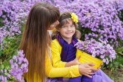 Schöne blonde Muttermutter mit ihrem netten lächelnden Tochtermädchen, das bunte Kleidung Zeit nah an purpurrotem flo zusammen ge Lizenzfreies Stockbild