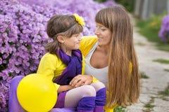 Schöne blonde Muttermutter mit ihrem netten lächelnden Tochtermädchen, das bunte Kleidung Zeit nah an purpurrotem flo zusammen ge Lizenzfreie Stockbilder