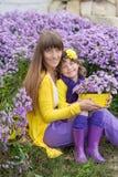 Schöne blonde Muttermutter mit ihrem netten lächelnden Tochtermädchen, das bunte Kleidung Zeit nah an purpurrotem flo zusammen ge Stockfoto
