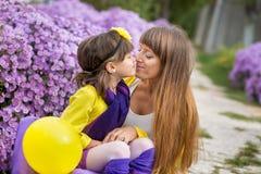 Schöne blonde Muttermutter mit ihrem netten lächelnden Tochtermädchen, das bunte Kleidung Zeit nah an purpurrotem flo zusammen ge Lizenzfreies Stockfoto