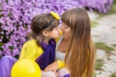 Schöne blonde Muttermutter mit ihrem netten lächelnden Tochtermädchen, das bunte Kleidung Zeit nah an purpurrotem flo zusammen ge Stockbilder