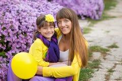 Schöne blonde Muttermutter mit ihrem netten lächelnden Tochtermädchen, das bunte Kleidung Zeit nah an purpurrotem flo zusammen ge Lizenzfreie Stockfotografie