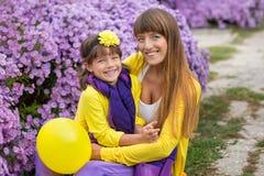 Schöne blonde Muttermutter mit ihrem netten lächelnden Tochtermädchen, das bunte Kleidung Zeit nah an purpurrotem flo zusammen ge Lizenzfreie Stockfotos
