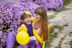 Schöne blonde Muttermutter mit ihrem netten lächelnden Tochtermädchen, das bunte Kleidung Zeit nah an purpurrotem flo zusammen ge Stockfotos