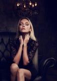 Schöne blonde mystische Frauenrechtschreibung, die auf schwarzem armchai sitzt Stockbild