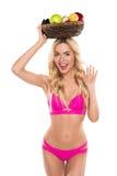 Schöne blonde nette Frau im rosa Bikini, der Korb mit Früchten wellenartig bewegt und hält Lizenzfreies Stockfoto