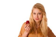 Schöne blonde nette kaukasische Frau isst ein großes rotes strawber Stockfoto