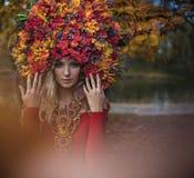 Schöne blonde Nymphe, die eindrucksvolle, bunte Krone trägt stockfoto
