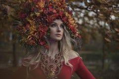 Schöne blonde Nymphe, die eindrucksvolle, bunte Krone trägt lizenzfreie stockbilder