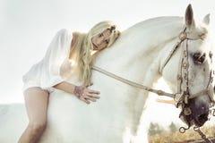 Schöne blonde Nymphe mit ihrem Pferd Stockfoto