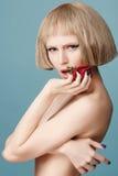 Schöne blonde Perücke mit einer roten Rose in ihrer Hand Stockbilder