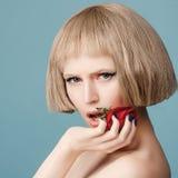 Schöne blonde Perücke mit einer roten Rose in ihrer Hand Stockfotografie